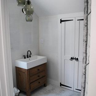 Modelo de cuarto de baño principal, rústico, pequeño, con lavabo sobreencimera, armarios tipo mueble, puertas de armario de madera oscura, encimera de cuarzo compacto, ducha empotrada, sanitario de dos piezas, baldosas y/o azulejos blancos, baldosas y/o azulejos de piedra y suelo de baldosas de porcelana