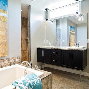 Modelo de cuarto de baño principal, costero, de tamaño medio, con armarios tipo mueble, puertas de armario de madera en tonos medios, bañera esquinera, ducha empotrada, baldosas y/o azulejos con efecto espejo, paredes grises, suelo de baldosas de porcelana, lavabo encastrado, encimera de granito, suelo multicolor y ducha abierta