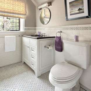 Example of a trendy white tile and subway tile gray floor bathroom design in New York with an undermount sink, white cabinets, granite countertops, a two-piece toilet and recessed-panel cabinets