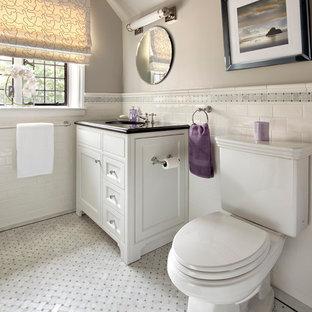 Foto de cuarto de baño actual con lavabo bajoencimera, puertas de armario blancas, encimera de granito, sanitario de dos piezas, baldosas y/o azulejos blancos, baldosas y/o azulejos de cemento, armarios con paneles empotrados y suelo gris