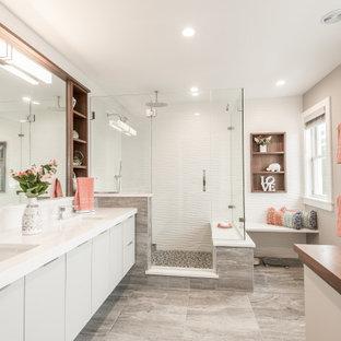 Großes Modernes Badezimmer En Suite mit flächenbündigen Schrankfronten, grauen Schränken, Eckdusche, weißen Fliesen, Keramikfliesen, beiger Wandfarbe, Keramikboden, Unterbauwaschbecken, Quarzwerkstein-Waschtisch, Falttür-Duschabtrennung, weißer Waschtischplatte und grauem Boden in Bridgeport