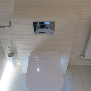 Photo of a large contemporary family bathroom in London with a wall mounted toilet, white tiles, ceramic tiles, white walls, ceramic flooring and white floors.