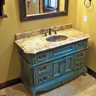 Imagen de cuarto de baño con ducha, rural, pequeño, con armarios tipo mueble, puertas de armario azules, paredes amarillas, suelo de piedra caliza, lavabo bajoencimera, encimera de granito y suelo beige