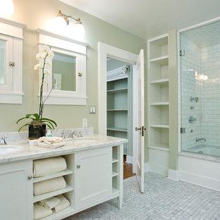 シカゴの中くらいのトラディショナルスタイルのおしゃれなマスターバスルーム (落し込みパネル扉のキャビネット、白いキャビネット、アルコーブ型浴槽、シャワー付き浴槽、白いタイル、セラミックタイル、緑の壁、モザイクタイル、アンダーカウンター洗面器、珪岩の洗面台) の写真