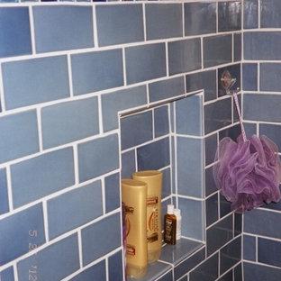 Idee per una stanza da bagno padronale chic di medie dimensioni con ante con bugna sagomata, WC monopezzo, piastrelle blu, piastrelle grigie, ante in legno bruno, vasca ad alcova, vasca/doccia, piastrelle in ceramica, pareti blu, lavabo sottopiano e top in granito