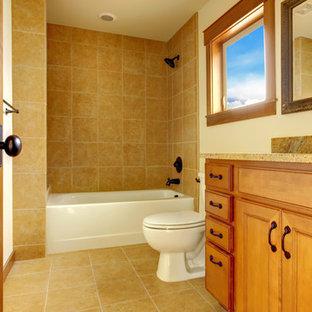 他の地域の中サイズのトラディショナルスタイルのおしゃれな子供用バスルーム (レイズドパネル扉のキャビネット、茶色いキャビネット、アルコーブ型浴槽、シャワー付き浴槽、分離型トイレ、ベージュのタイル、磁器タイル、ベージュの壁、磁器タイルの床、アンダーカウンター洗面器、御影石の洗面台、ベージュの床、シャワーカーテン、ベージュのカウンター) の写真