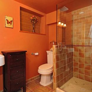 Esempio di una stanza da bagno con doccia stile americano con lavabo a colonna, consolle stile comò, ante in legno bruno, WC a due pezzi, piastrelle multicolore, piastrelle in ceramica, pareti arancioni e pavimento in gres porcellanato