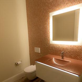 Diseño de cuarto de baño minimalista, pequeño, con armarios tipo mueble, puertas de armario blancas, sanitario de pared, baldosas y/o azulejos naranja, baldosas y/o azulejos de vidrio, paredes beige, suelo de baldosas de porcelana, lavabo integrado y encimera de acrílico
