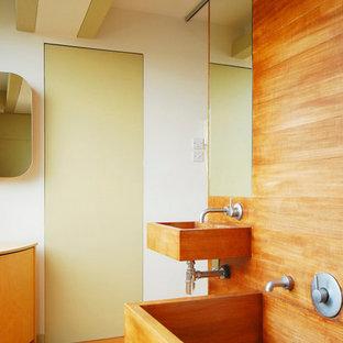 Modelo de cuarto de baño principal, actual, grande, con lavabo suspendido, armarios tipo mueble, puertas de armario de madera oscura, encimera de madera, bañera japonesa, paredes blancas y suelo de linóleo