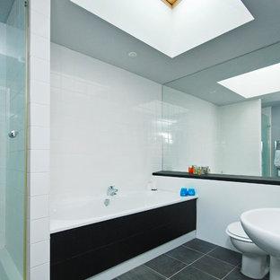 Modelo de cuarto de baño con ducha, moderno, de tamaño medio, con lavabo con pedestal, armarios con paneles lisos, encimera de ónix, bañera encastrada sin remate, ducha esquinera, sanitario de pared, baldosas y/o azulejos blancos, baldosas y/o azulejos de cerámica, paredes grises y suelo de pizarra