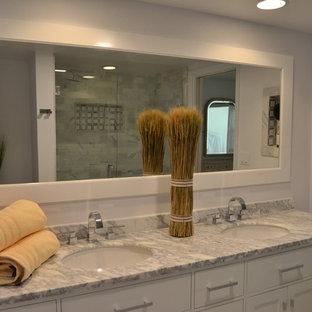Immagine di una stanza da bagno con doccia classica di medie dimensioni con ante con riquadro incassato, ante bianche, doccia alcova, piastrelle grigie, piastrelle di marmo, pareti grigie, lavabo sottopiano, top in granito, porta doccia a battente, top grigio e due lavabi