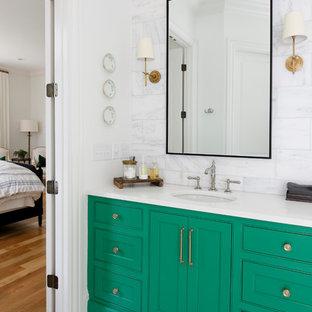 Inredning av ett klassiskt en-suite badrum, med luckor med profilerade fronter, gröna skåp, vit kakel, vita väggar, marmorgolv, ett undermonterad handfat och vitt golv
