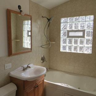 Kleines Shabby-Look Badezimmer mit profilierten Schrankfronten, hellen Holzschränken, Badewanne in Nische, Duschnische, Wandtoilette mit Spülkasten, beigefarbenen Fliesen, Keramikfliesen, beiger Wandfarbe, Keramikboden, Einbauwaschbecken, weißem Boden und Duschvorhang-Duschabtrennung in Chicago