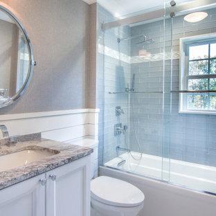Exempel på ett mellanstort modernt beige beige badrum för barn, med luckor med infälld panel, vita skåp, ett badkar i en alkov, en toalettstol med separat cisternkåpa, blå kakel, glaskakel, beige väggar, klinkergolv i porslin, ett undermonterad handfat, granitbänkskiva, flerfärgat golv och dusch med skjutdörr