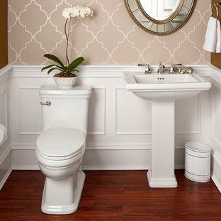 Новый формат декора квартиры: маленькая ванная комната в классическом стиле с унитазом-моноблоком, коричневыми стенами, темным паркетным полом, душевой кабиной, раковиной с пьедесталом, столешницей из нержавеющей стали и коричневым полом