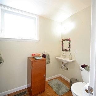 Immagine di una stanza da bagno tradizionale con ante lisce, ante marroni, vasca ad alcova, vasca/doccia, WC a due pezzi, pareti verdi, pavimento in bambù e lavabo sospeso