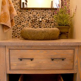 Ejemplo de cuarto de baño con ducha, marinero, pequeño, con lavabo sobreencimera, armarios tipo mueble, puertas de armario de madera clara, encimera de granito, baldosas y/o azulejos multicolor, suelo de baldosas tipo guijarro y paredes beige