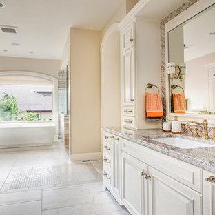 Immagine di una grande stanza da bagno padronale classica con ante con bugna sagomata, ante bianche, vasca freestanding, pareti beige, lavabo sottopiano, top in granito, piastrelle rosa e piastrelle di vetro