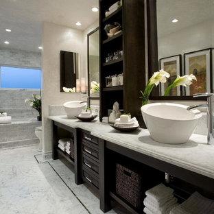 Bild på ett stort funkis en-suite badrum, med öppna hyllor, skåp i mörkt trä, ett undermonterat badkar, vit kakel, marmorkakel, beige väggar, marmorgolv, ett fristående handfat, marmorbänkskiva och grått golv