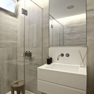 Inspiration for a mid-sized modern 3/4 brown tile, gray tile and porcelain tile porcelain tile and multicolored floor alcove shower remodel in New York with a wall-mount sink, quartz countertops and a hinged shower door