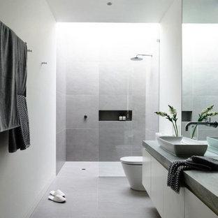 Новый формат декора квартиры: большая главная ванная комната в стиле модернизм с плоскими фасадами, белыми фасадами, душем без бортиков, серой плиткой, цементной плиткой, белыми стенами, бетонным полом, настольной раковиной, столешницей из бетона, серым полом и открытым душем