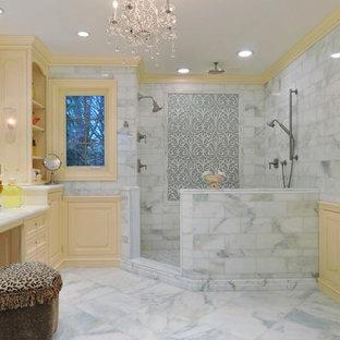Bild på ett stort vintage en-suite badrum, med gula skåp, en hörndusch, vit kakel, stenkakel, gula väggar, marmorgolv, en toalettstol med separat cisternkåpa, marmorbänkskiva och luckor med infälld panel