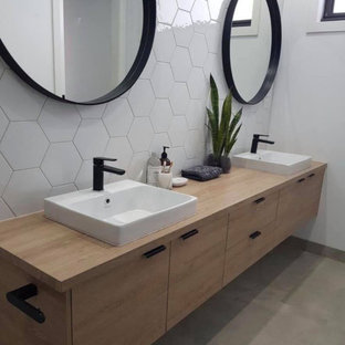 Example of a mid-sized minimalist master white tile and porcelain tile concrete floor and gray floor bathroom design in Austin with flat-panel cabinets, light wood cabinets, white walls, a drop-in sink, wood countertops and brown countertops