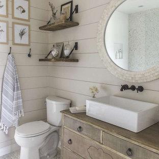 Идея дизайна: ванная комната среднего размера в стиле неоклассика (современная классика) с фасадами островного типа, фасадами цвета дерева среднего тона, раздельным унитазом, серыми стенами, душевой кабиной, настольной раковиной, столешницей из дерева, серым полом, коричневой столешницей, тумбой под одну раковину, напольной тумбой и стенами из вагонки