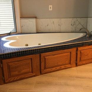 Immagine di una stanza da bagno padronale classica di medie dimensioni con ante con bugna sagomata, ante in legno scuro, vasca da incasso, piastrelle bianche, piastrelle di marmo, pareti grigie, parquet chiaro, top piastrellato e pavimento beige