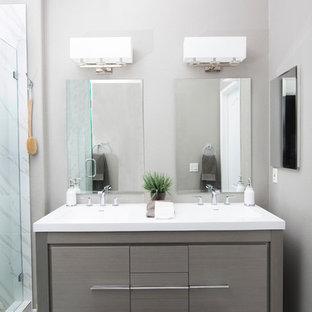 サンディエゴの中くらいのコンテンポラリースタイルのおしゃれなマスターバスルーム (フラットパネル扉のキャビネット、グレーのキャビネット、グレーのタイル、白いタイル、石スラブタイル、グレーの壁、アンダーカウンター洗面器、アルコーブ型シャワー、大理石の床、クオーツストーンの洗面台) の写真