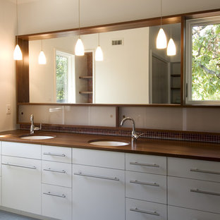 Mid-sized minimalist master blue tile, brown tile and mosaic tile mosaic tile floor and blue floor bathroom photo in Austin with wood countertops, flat-panel cabinets, white cabinets, beige walls, an undermount sink and brown countertops