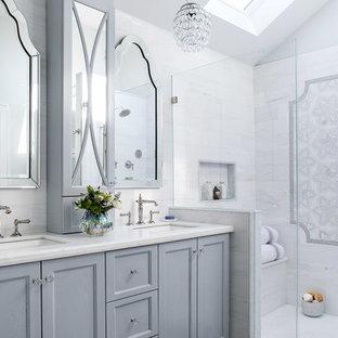 Inredning av ett klassiskt mellanstort vit vitt en-suite badrum, med en hörndusch, en toalettstol med hel cisternkåpa, vit kakel, marmorkakel, klinkergolv i porslin, bänkskiva i kvartsit, dusch med gångjärnsdörr, luckor med infälld panel, grå skåp, vita väggar, ett undermonterad handfat och grått golv