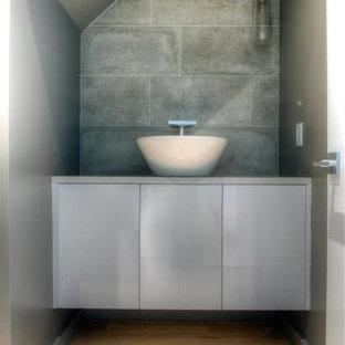 Esempio di una grande stanza da bagno padronale design con ante lisce, ante grigie, piastrelle grigie, pareti grigie, parquet chiaro, lavabo a colonna, top in cemento, piastrelle in pietra e pavimento beige