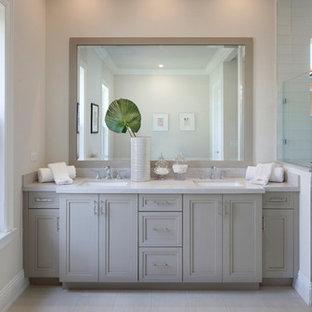 Ispirazione per una stanza da bagno padronale classica di medie dimensioni con ante con riquadro incassato, ante beige, doccia alcova, piastrelle bianche, piastrelle di vetro, pareti bianche, pavimento in gres porcellanato, lavabo sottopiano, top in marmo, pavimento beige e porta doccia a battente