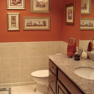 ボルチモアの中サイズのトラディショナルスタイルのおしゃれな浴室 (レイズドパネル扉のキャビネット、濃色木目調キャビネット、赤い壁、セラミックタイルの床、アンダーカウンター洗面器、御影石の洗面台、一体型トイレ、ベージュのタイル、セラミックタイル、ベージュの床) の写真