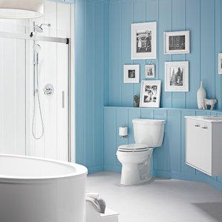 Diseño de cuarto de baño principal, de tamaño medio, con lavabo integrado, puertas de armario blancas, bañera exenta, ducha empotrada, sanitario de dos piezas, paredes azules y armarios con paneles lisos