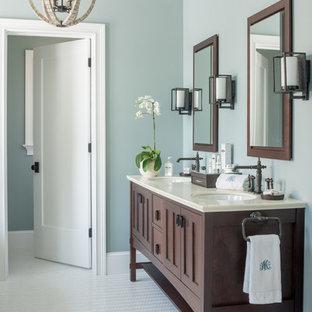 Diseño de cuarto de baño principal, de estilo americano, grande, con lavabo bajoencimera, armarios tipo mueble, baldosas y/o azulejos blancos, paredes azules, suelo de baldosas de porcelana y puertas de armario de madera en tonos medios