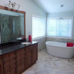 Foto di una stanza da bagno con lavabo sottopiano, ante con riquadro incassato, ante in legno bruno, top in onice, vasca freestanding, pareti blu e pavimento in marmo