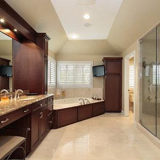 Klassisk inredning av ett mycket stort flerfärgad flerfärgat en-suite badrum, med luckor med infälld panel, skåp i mörkt trä, ett hörnbadkar, en dusch i en alkov, beige kakel, porslinskakel, beige väggar, klinkergolv i porslin, ett undermonterad handfat, granitbänkskiva, beiget golv och dusch med gångjärnsdörr
