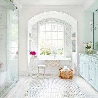 Modelo de cuarto de baño principal, tradicional, con lavabo bajoencimera, bañera exenta, baldosas y/o azulejos blancos, baldosas y/o azulejos de piedra, suelo de mármol, armarios con rebordes decorativos y paredes blancas