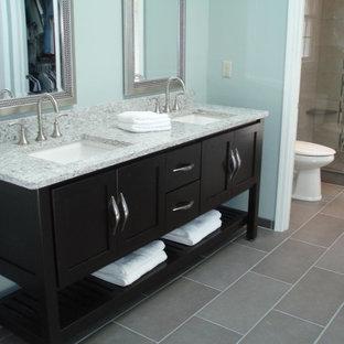 Ejemplo de cuarto de baño principal, clásico, de tamaño medio, con armarios con paneles empotrados, puertas de armario negras, ducha esquinera, paredes azules, suelo de baldosas de cerámica, lavabo encastrado, encimera de granito, suelo gris y ducha con puerta con bisagras