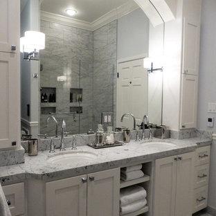 Modelo de cuarto de baño infantil, exótico, de tamaño medio, con armarios estilo shaker, puertas de armario blancas, ducha empotrada, baldosas y/o azulejos grises, losas de piedra, paredes grises, suelo de mármol, lavabo bajoencimera y encimera de mármol