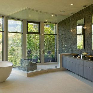 Idee per una stanza da bagno design con lavabo a bacinella, ante lisce, ante grigie, top in quarzo composito, vasca freestanding, doccia doppia, WC monopezzo, piastrelle grigie e piastrelle in pietra