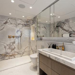 Idée de décoration pour une salle de bain design avec un placard à porte plane, des portes de placard marrons, un WC suspendu, du carrelage en marbre, un mur gris, un lavabo posé, un plan de toilette en marbre, un sol blanc et une cabine de douche à porte battante.