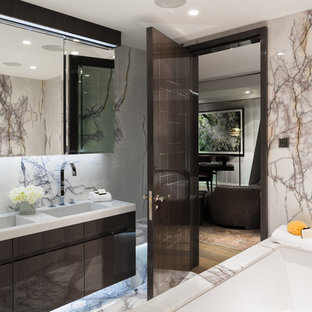 Design ideas for a contemporary ensuite bathroom in London with flat-panel cabinets, brown cabinets, a submerged bath, beige walls, marble flooring and an integrated sink.