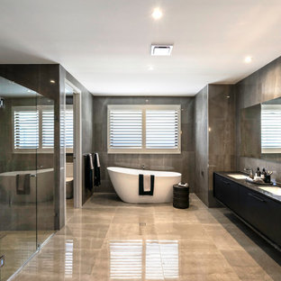 Contemporary bathroom in Sydney with flat-panel cabinets, black cabinets, a freestanding tub, an alcove shower, gray tile, an undermount sink, grey floor, a hinged shower door, black benchtops, an enclosed toilet, a double vanity and a floating vanity.