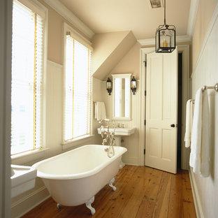 Immagine di una stanza da bagno padronale country di medie dimensioni con lavabo a colonna, vasca con piedi a zampa di leone, pareti beige e pavimento in legno massello medio