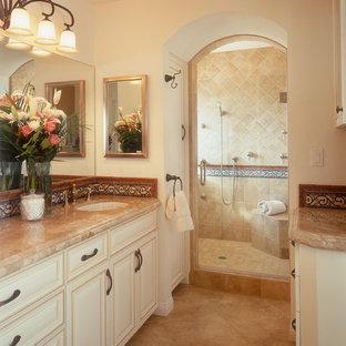 Immagine di una stanza da bagno design con lavabo sottopiano, ante con bugna sagomata, ante beige, doccia alcova, piastrelle beige e piastrelle in travertino