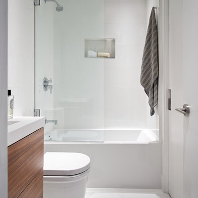 Bathroom - small modern master white tile and ceramic tile ceramic tile and white floor bathroom idea in San Francisco with flat-panel cabinets, dark wood cabinets, a one-piece toilet, white walls, an integrated sink, quartz countertops, a hinged shower door and white countertops