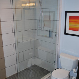 Small modern 3/4 bathroom in Calgary with shaker cabinets, dark wood cabinets, an alcove shower, a two-piece toilet, beige tile, porcelain tile, beige walls, laminate floors, an undermount sink, solid surface benchtops, beige floor and a hinged shower door.
